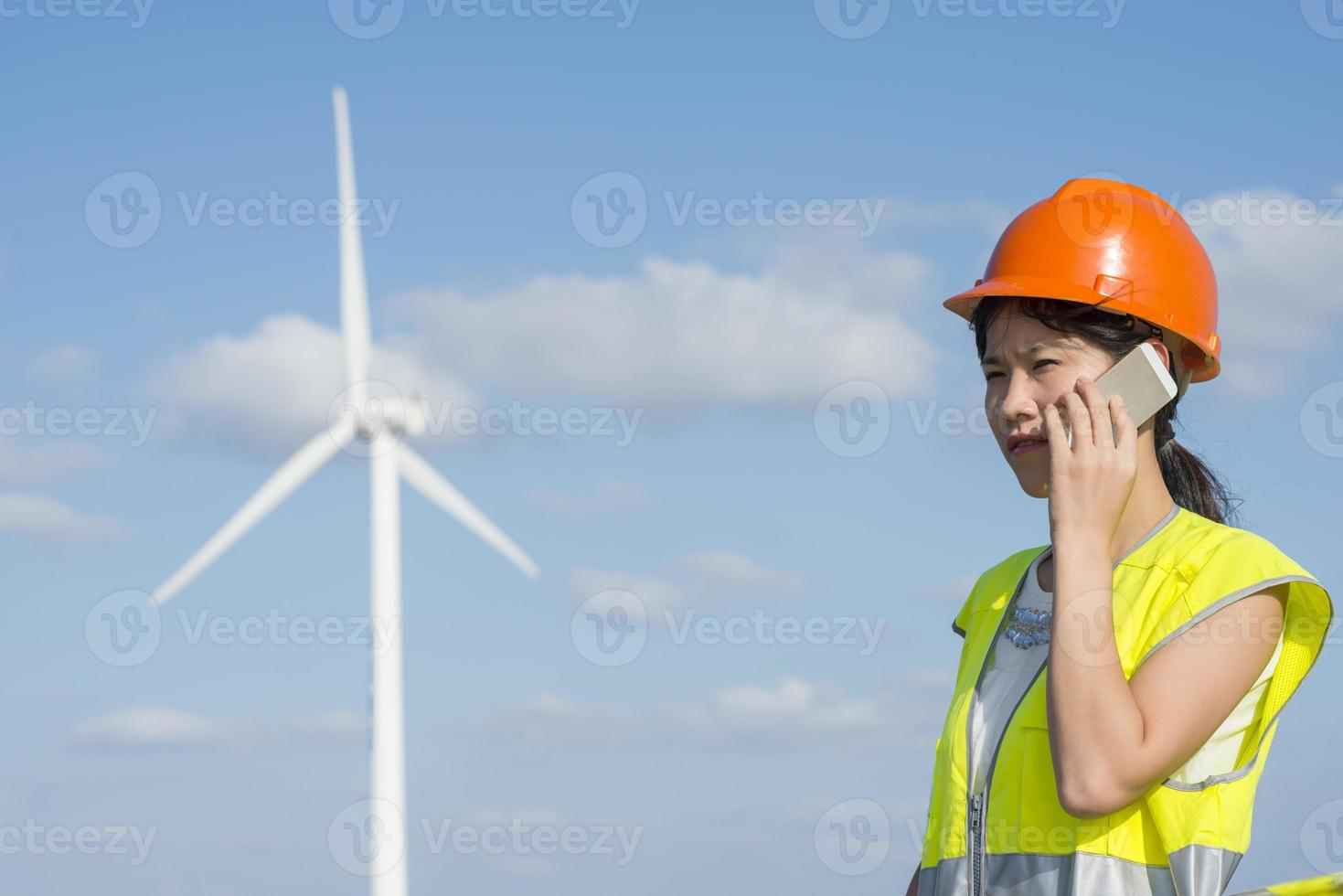 Engineer talking on phone by windmill photo