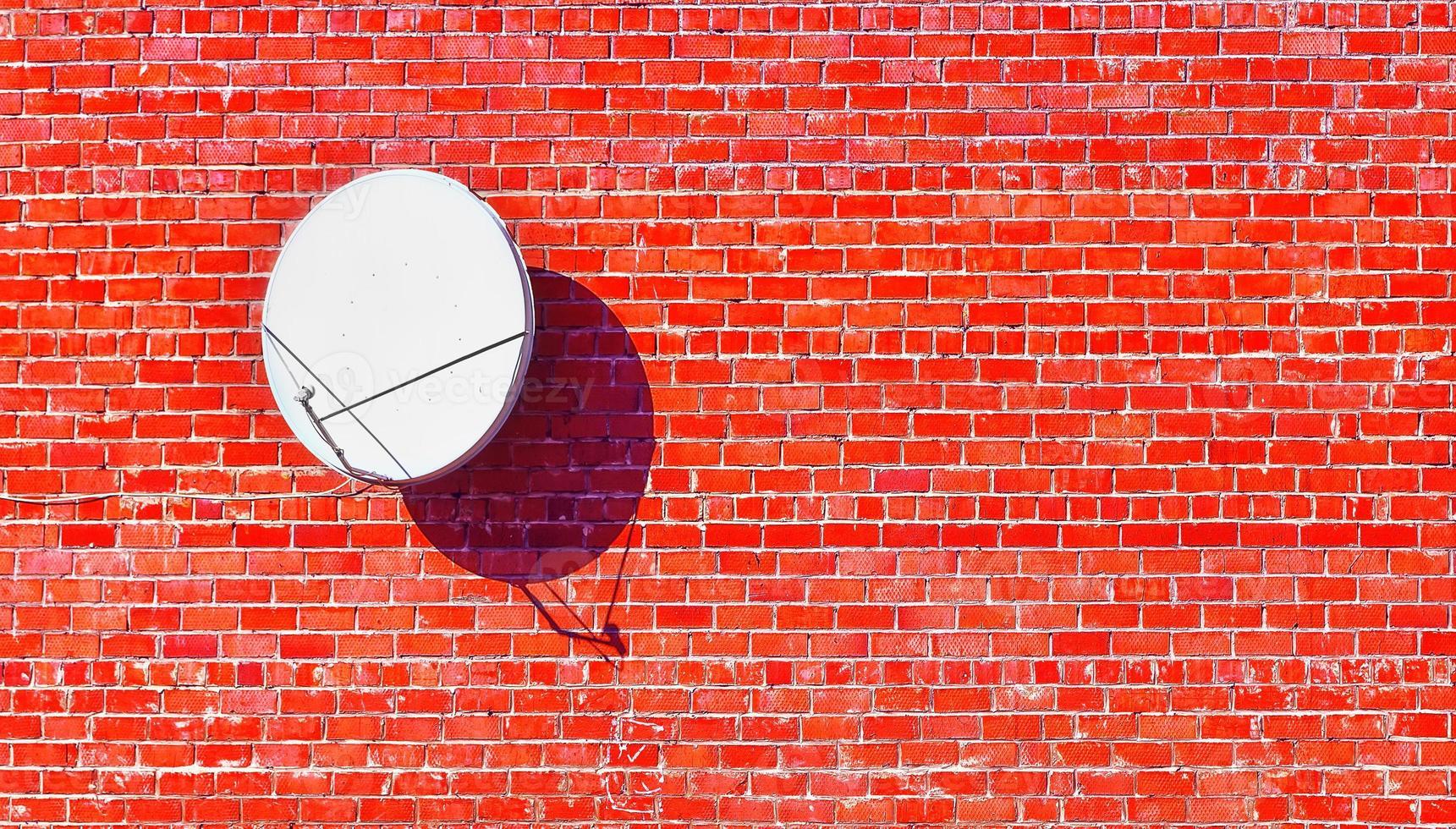 satellite dish red brick wall shadow photo