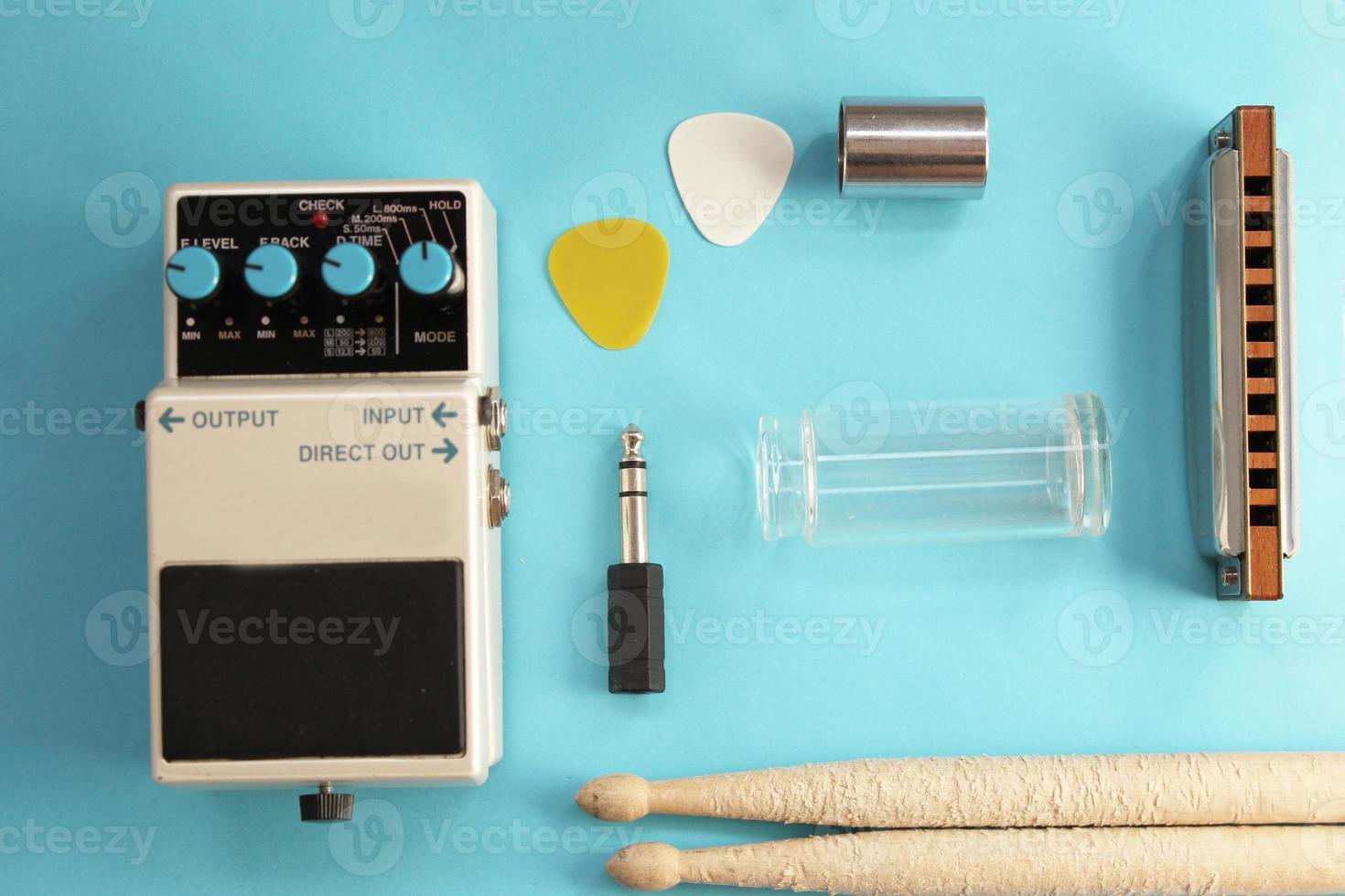 Guitar pedal, drum sticks, harmonica, audio plug and guitar picks photo