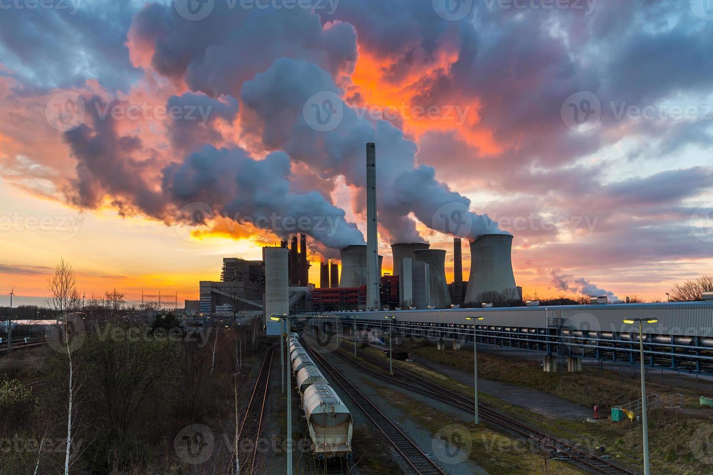 central eléctrica de carbón con ardiente cielo al atardecer foto