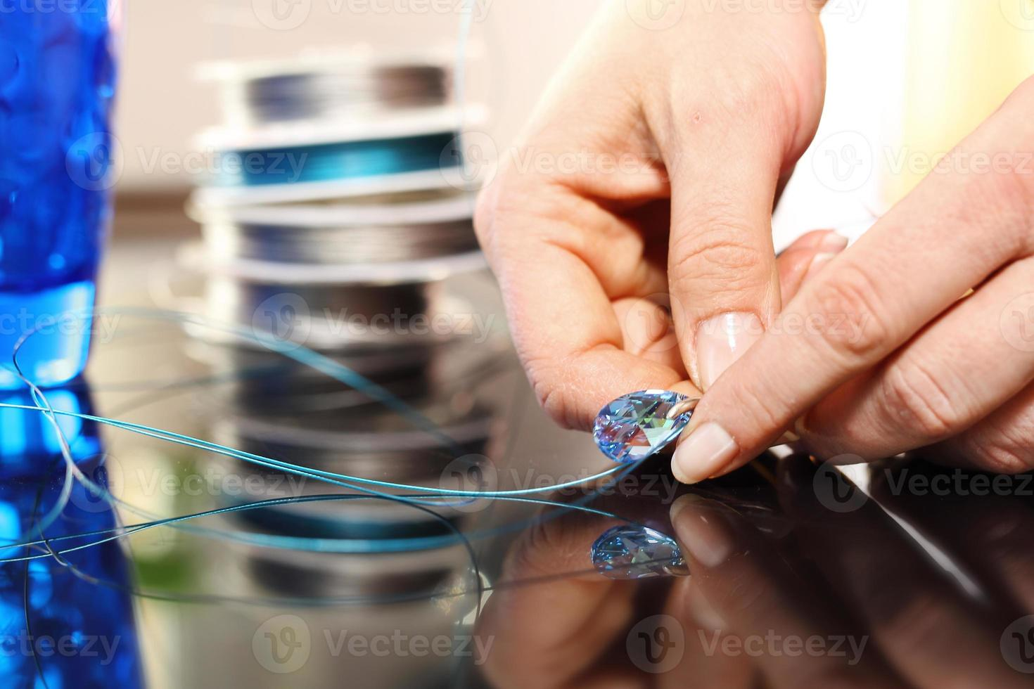Woman hands a jeweler while working on jewelery photo