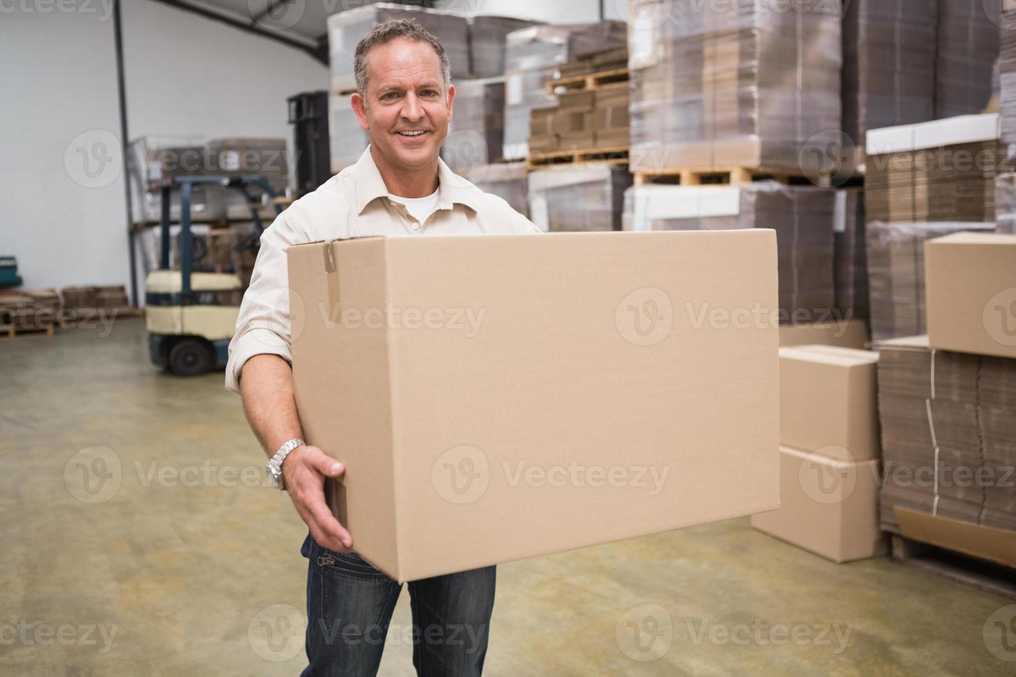 Portrait of worker carrying box photo