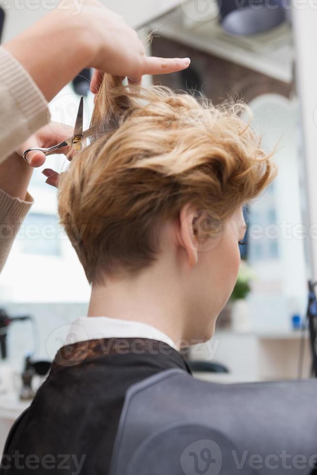 peluquería sonriente cortando el cabello de los clientes foto