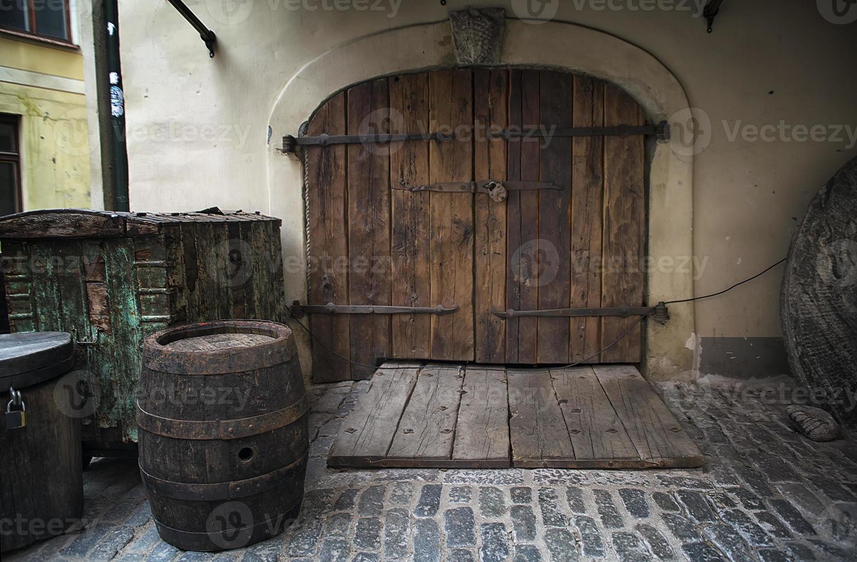 Antigua puerta de madera oxidada con barril como telón de fondo foto