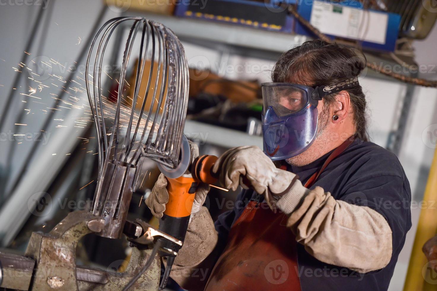 Trabajador de metal pulido con chispas en taller foto