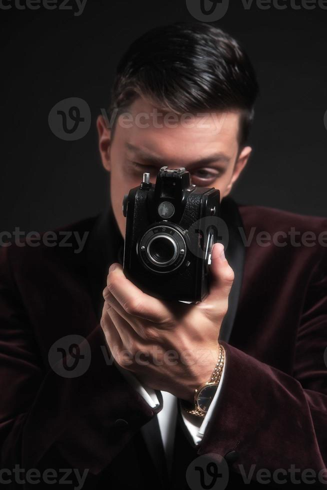 Hombre de negocios bien vestido tomando foto con cámara vintage.
