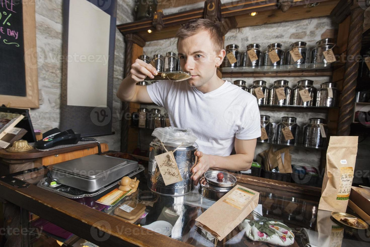 verkoper ruikende thee in de winkel foto