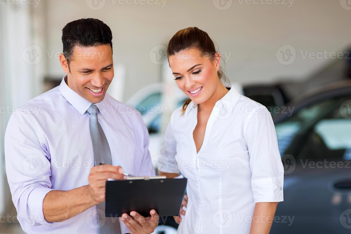vehicle dealership principal and saleswoman looking at clipboard photo