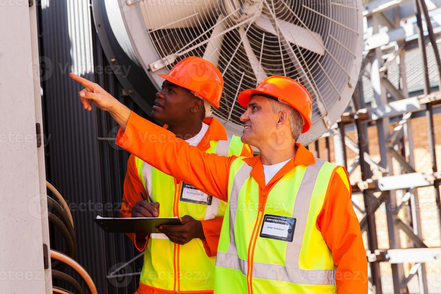 técnico senior y joven electricista trabajando en planta de energía foto