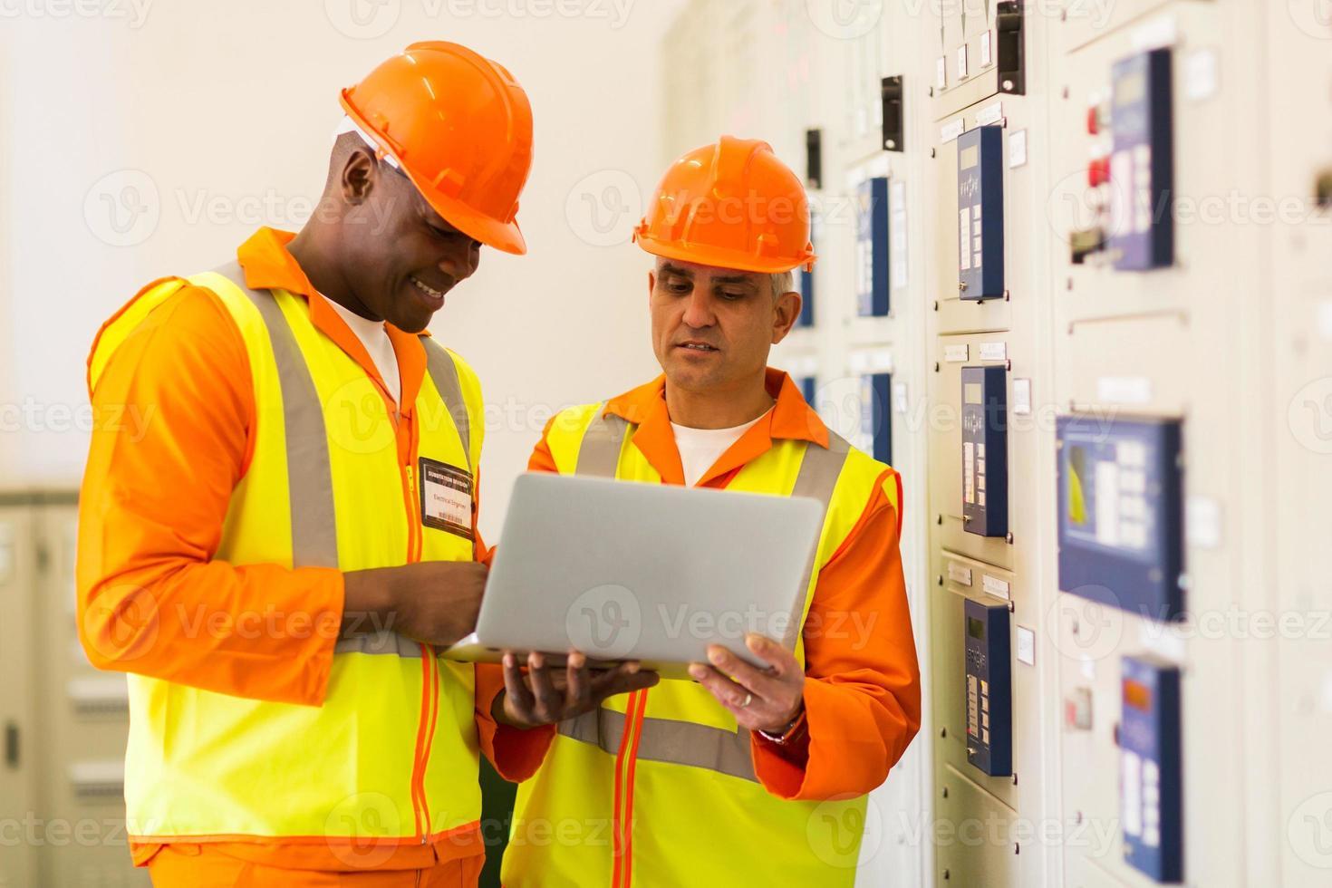 Técnicos que usan la computadora portátil en la sala de control foto