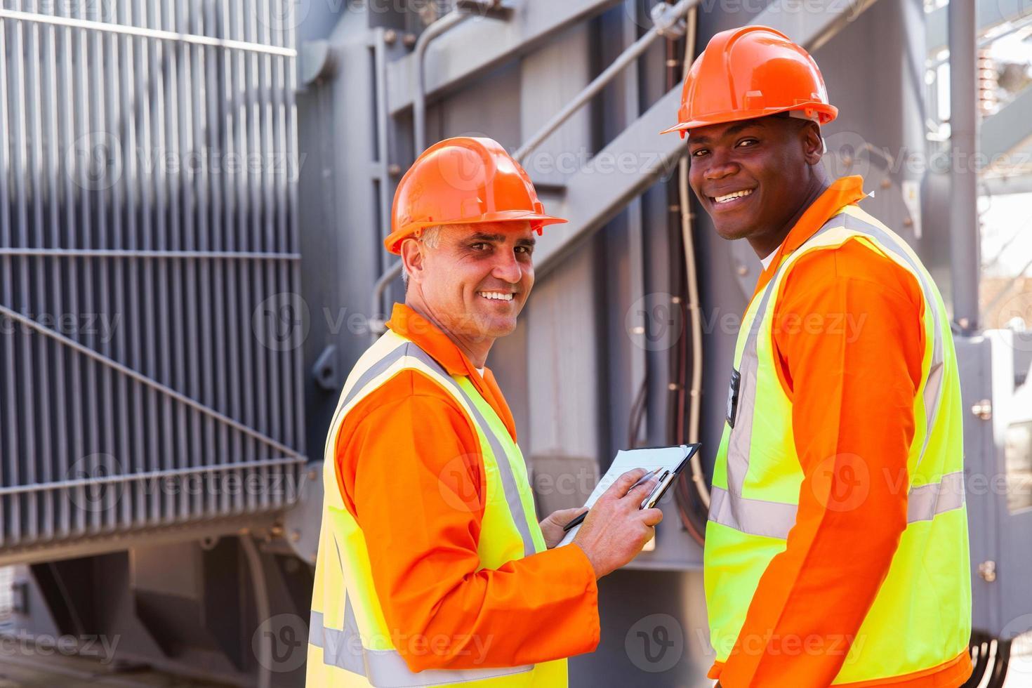 electricistas mirando hacia atrás en subestación eléctrica foto