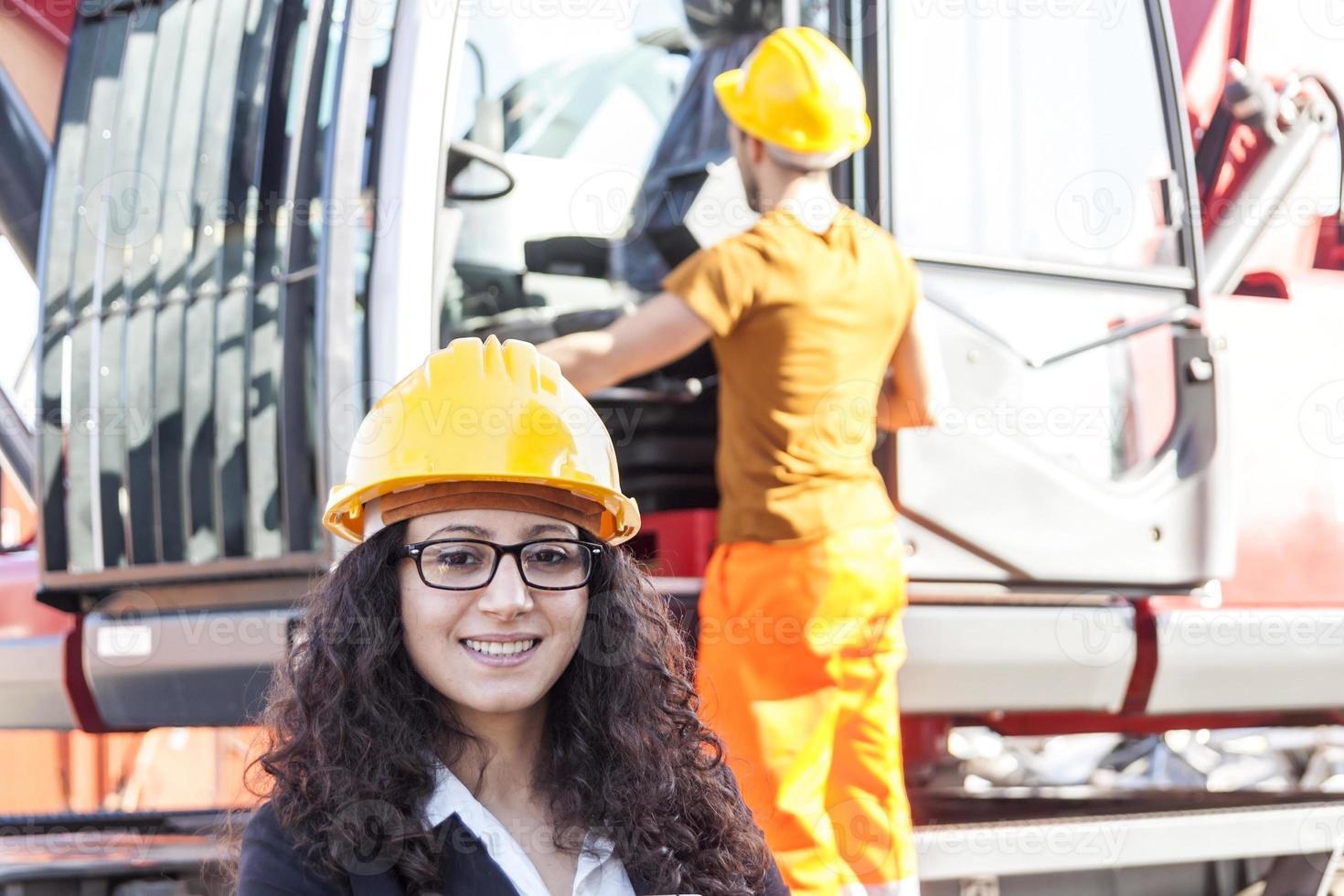 joven ingeniera posando en depósito de chatarra con un trabajador foto