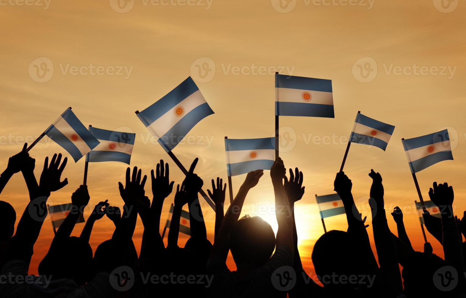 Silhouettes of People Holding Flag of Argentina photo