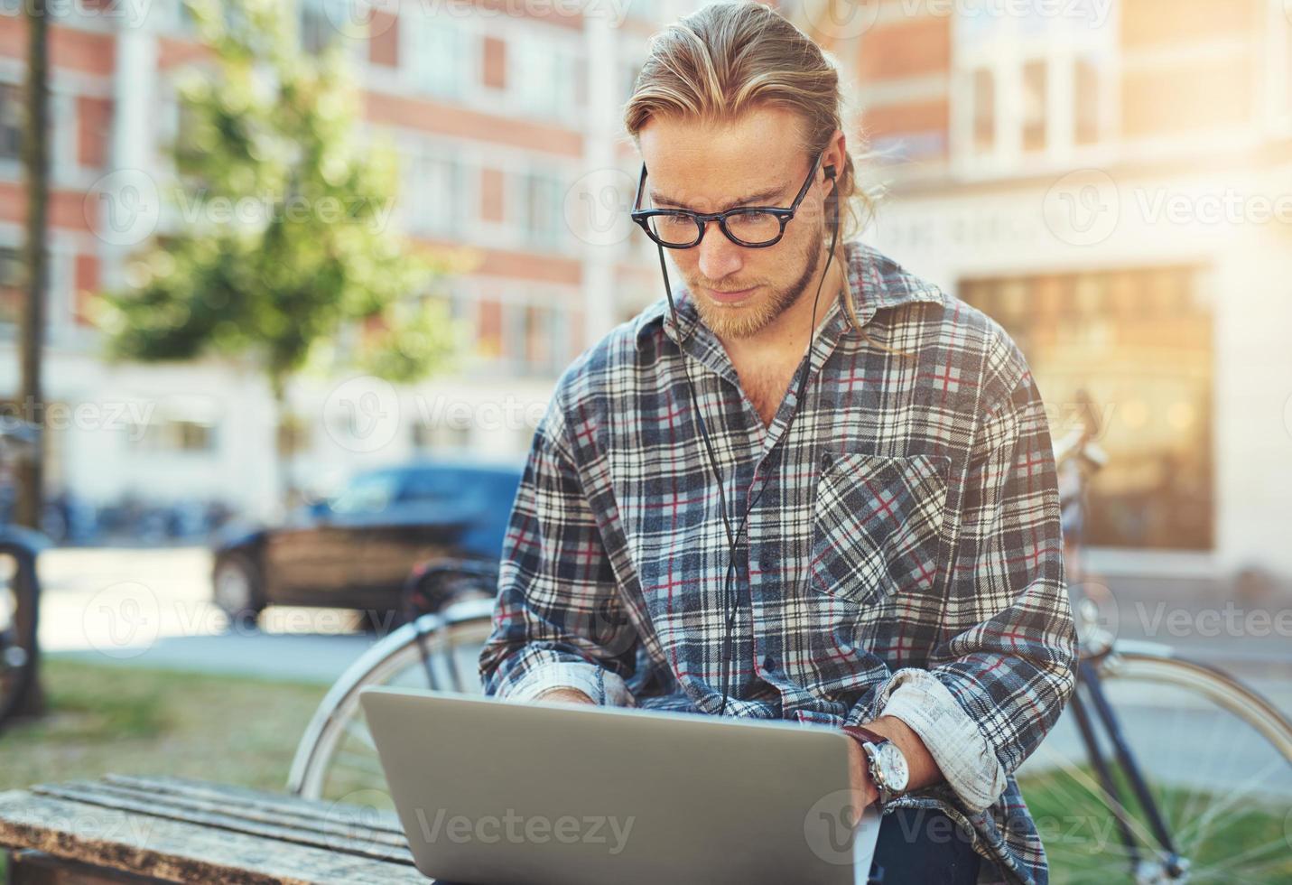 joven concentrado con su computadora portátil foto