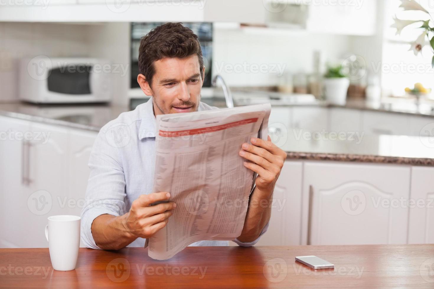 Hombre concentrado leyendo el periódico en la cocina foto