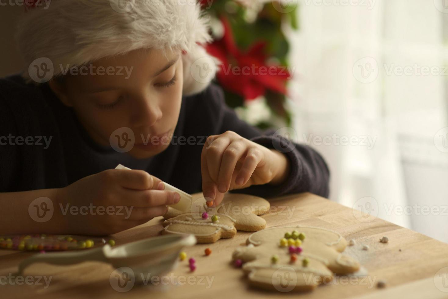 child concentrated prepares gingerbread man for christmas photo
