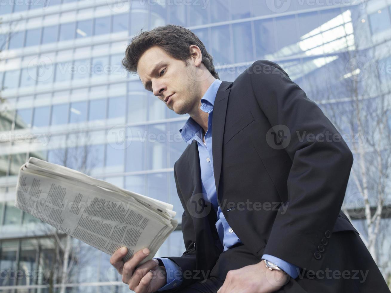 Businessman Reading Newspaper Outdoors photo