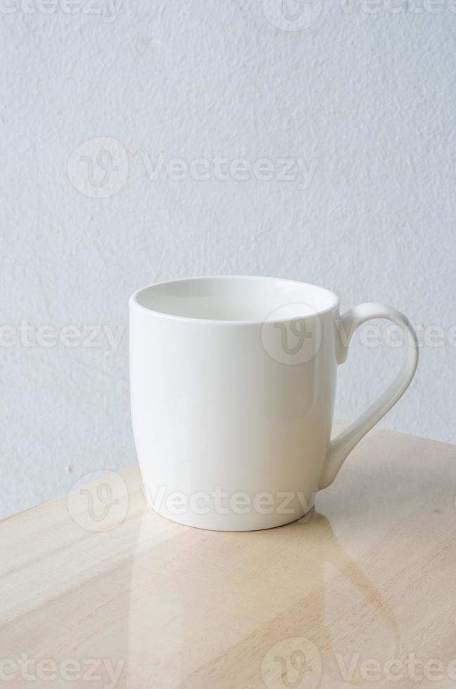 taza blanca en mesa de madera foto
