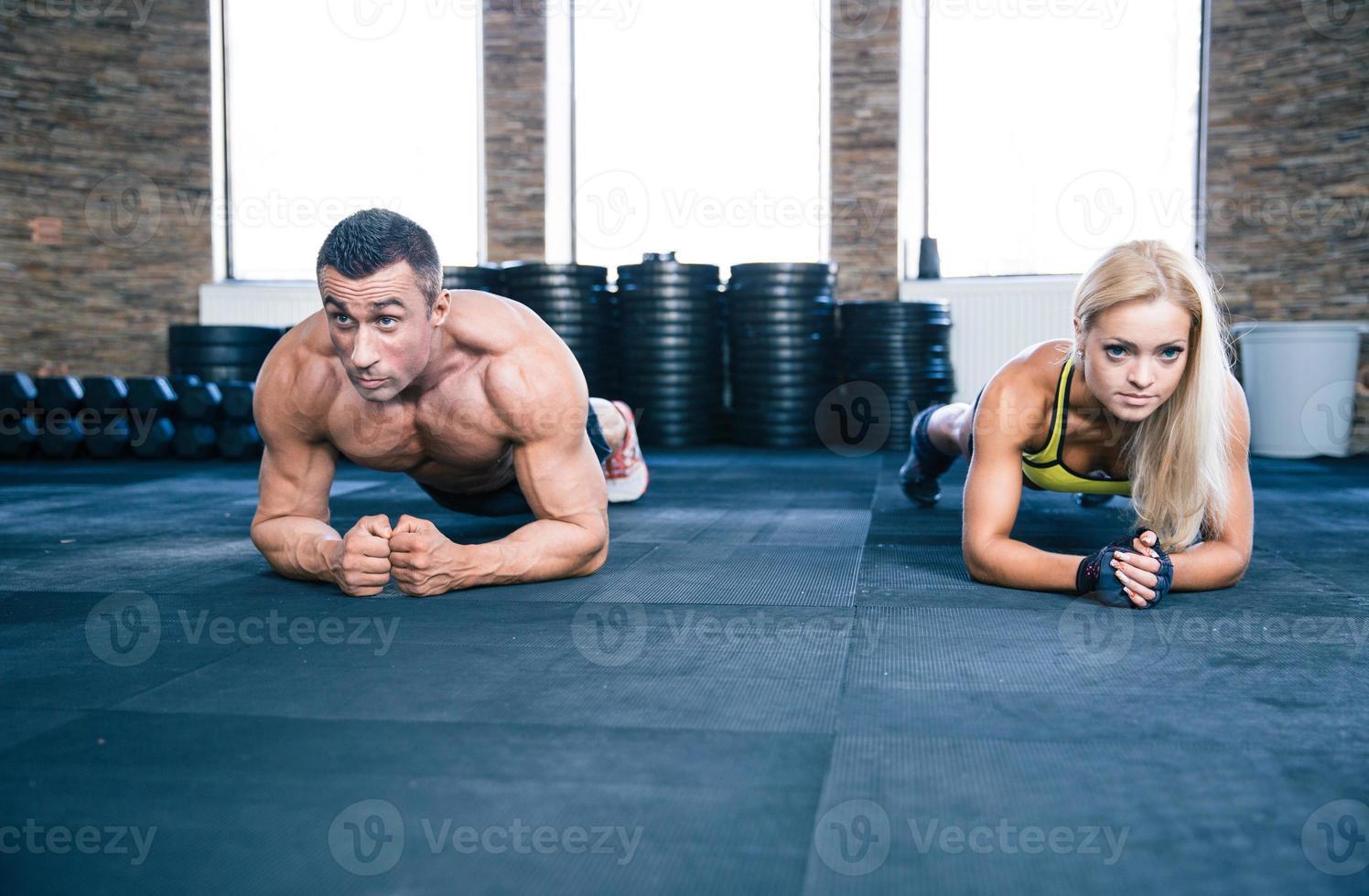 entrenamiento de hombre musculoso y mujer fuerte en el gimnasio foto
