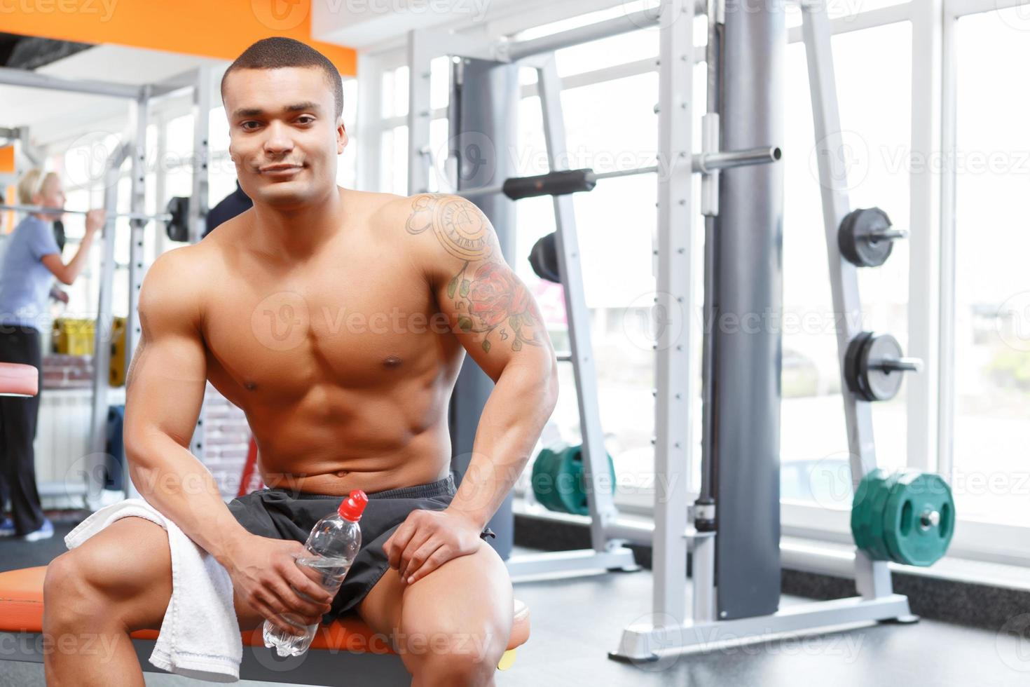 hombre sentado con una botella y una toalla en el gimnasio foto