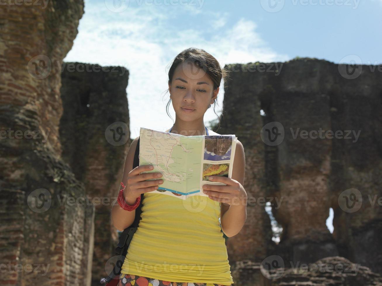 mujer leyendo la guía con ruinas antiguas en segundo plano. foto