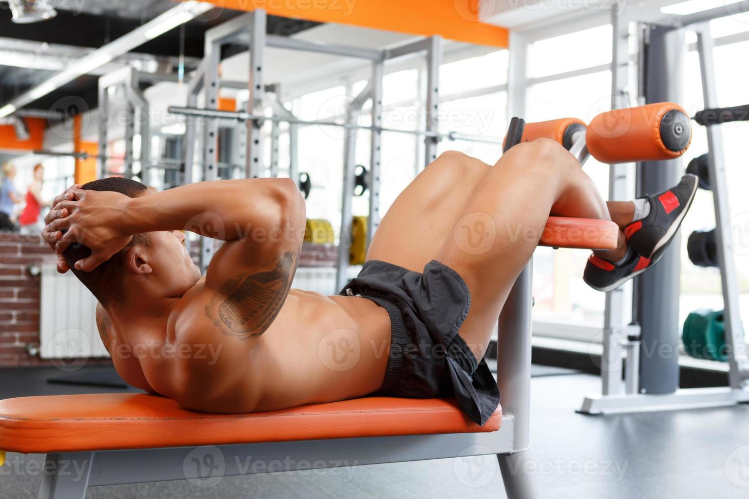 Young pleasant man doing abdominal crunches in gym photo