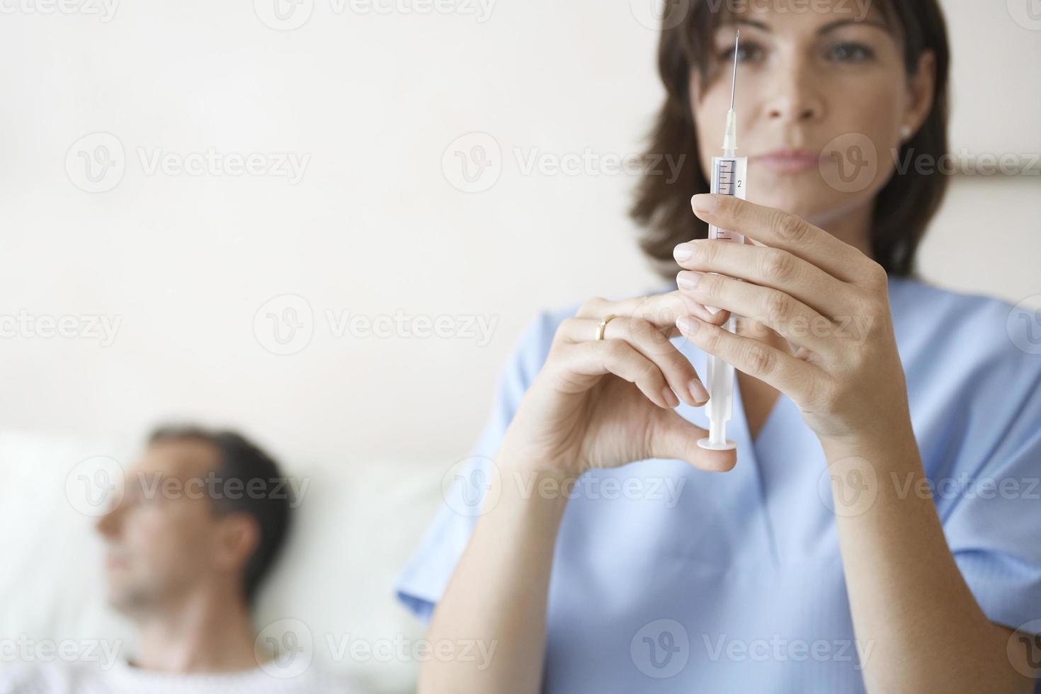 enfermera preparando la jeringa para inyección por paciente foto