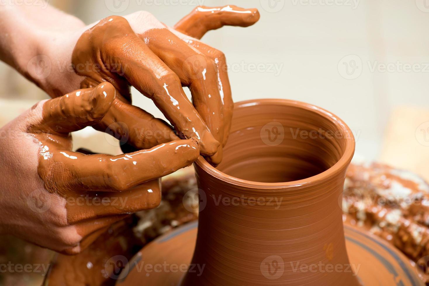 mains d'un potier, créant un pot en terre photo