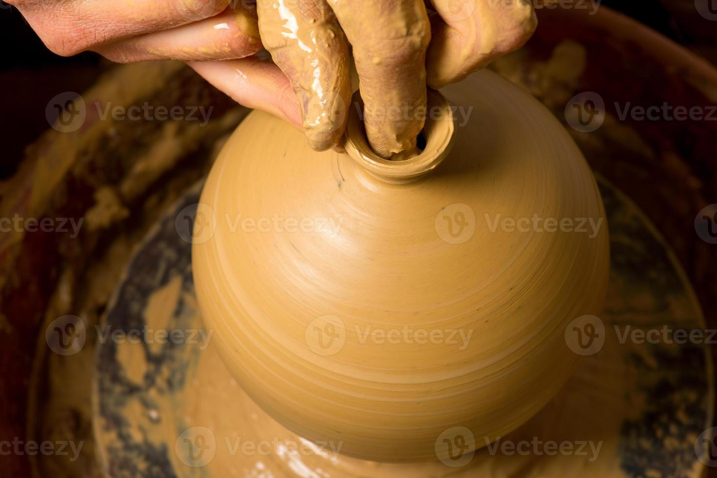 hands of a potter, creating an earthen jar photo