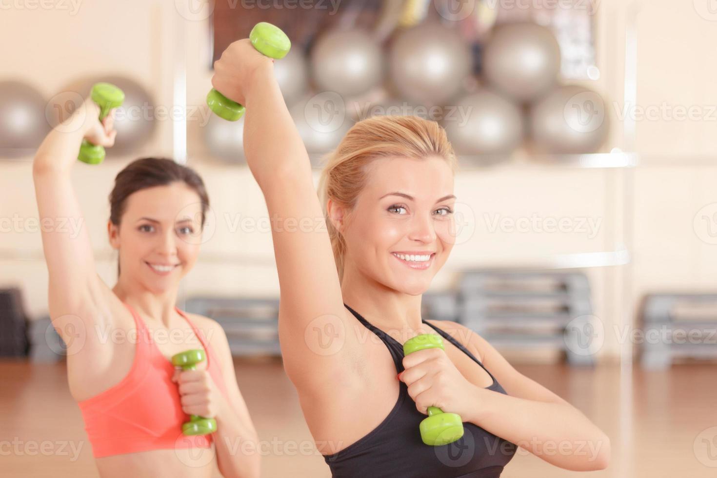 pareja de mujeres haciendo pesas fitness foto