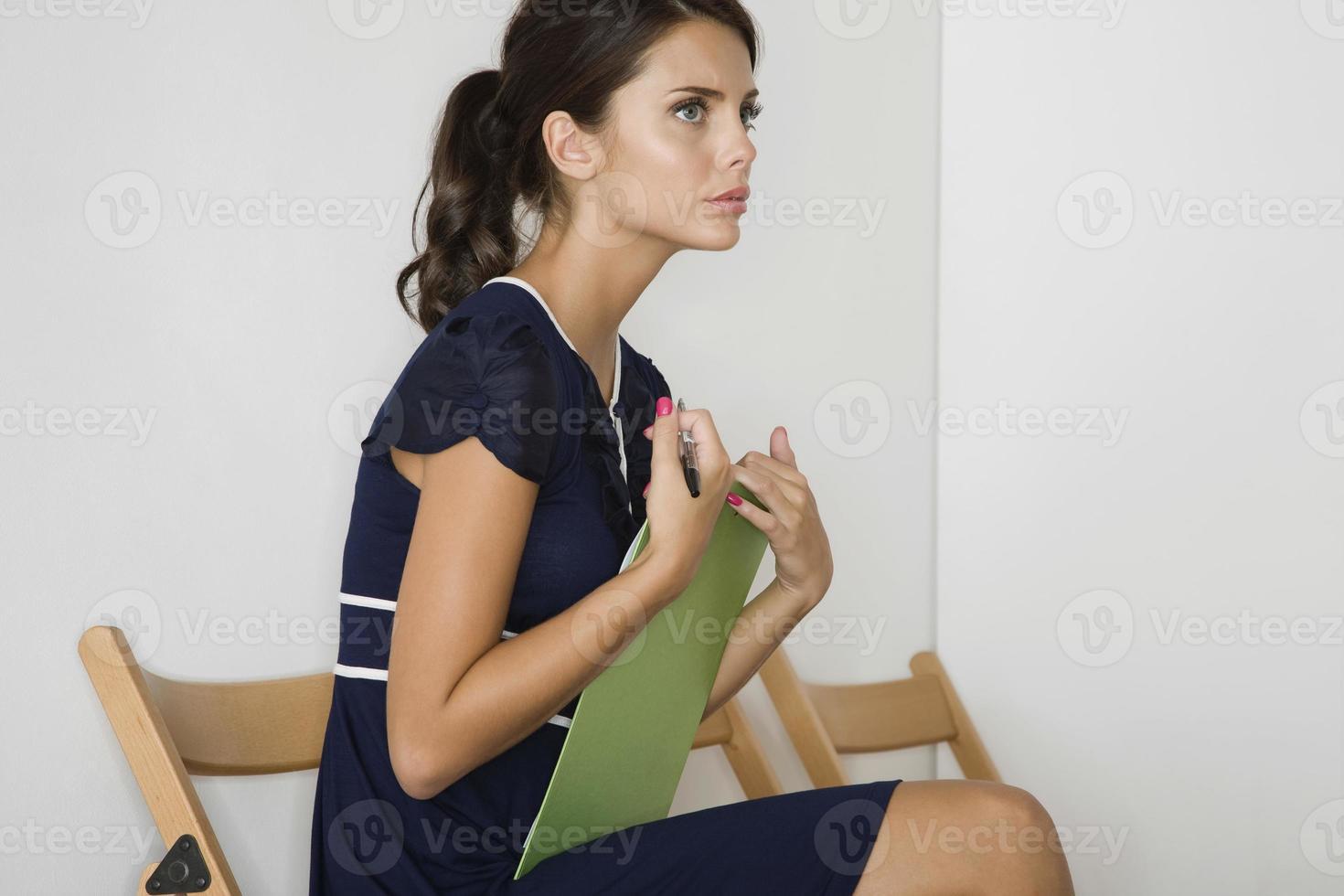 mujer pensativa en vestido azul con portapapeles foto