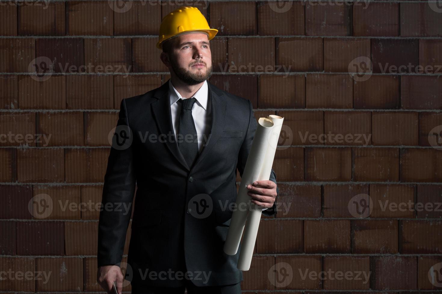 joven trabajador de la construcción con blueprint foto
