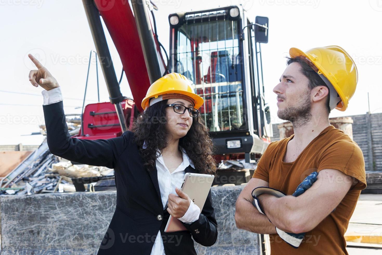 joven ingeniera habla sobre trabajar con un trabajador foto
