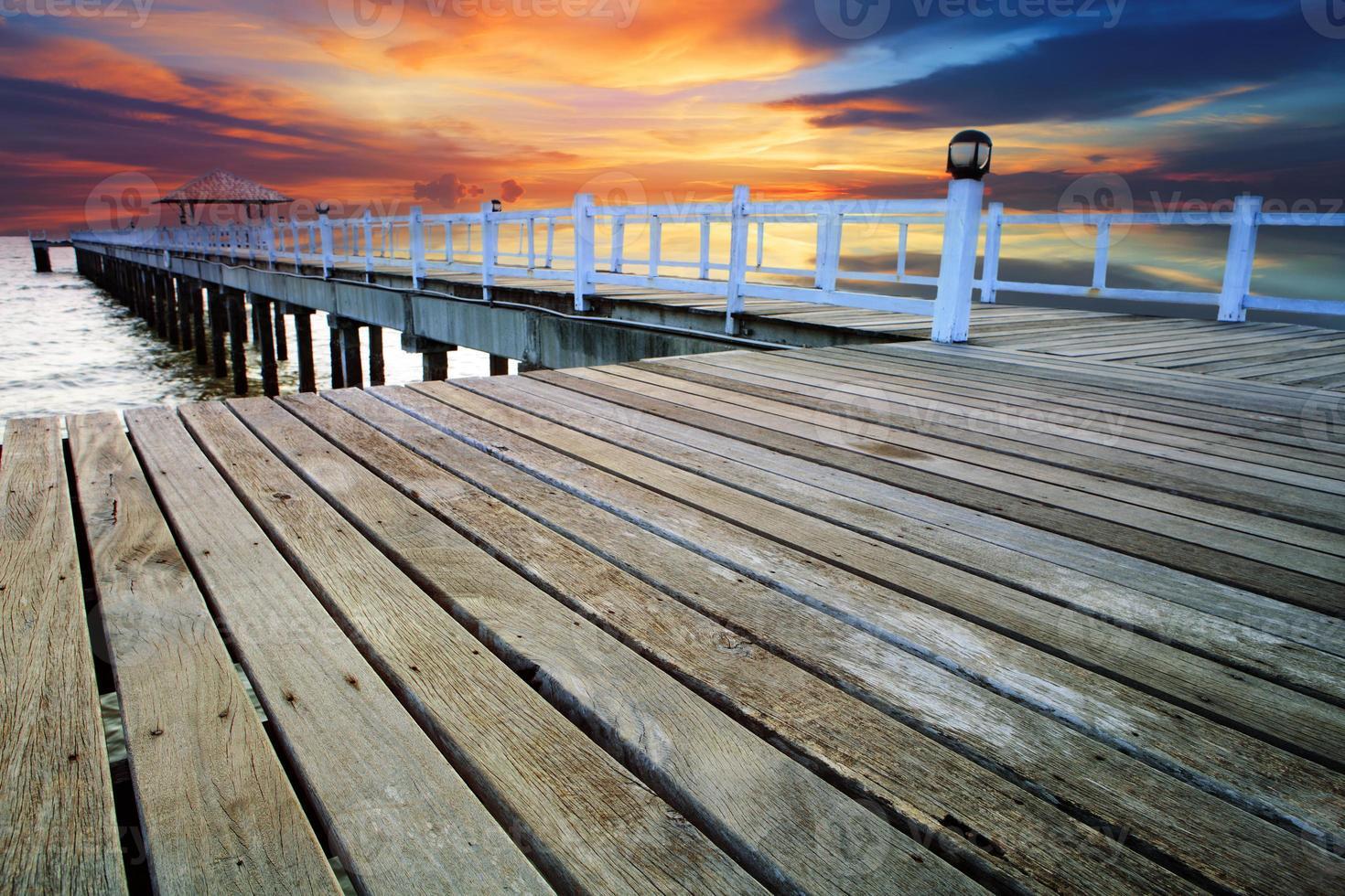 hermoso viejo puente de madera en la playa con puesta de sol cielo foto