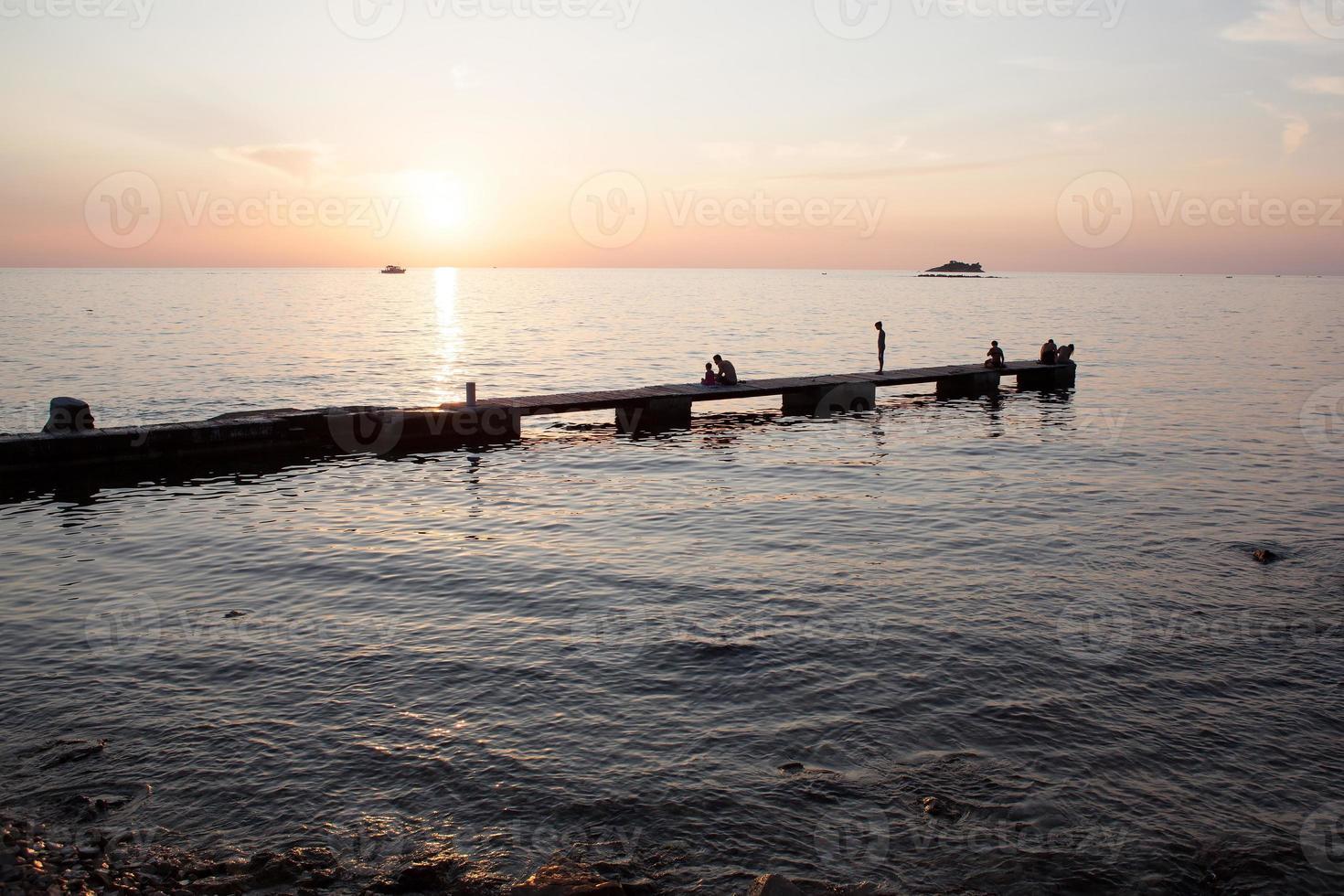 puesta de sol y silueta de personas en el muelle foto