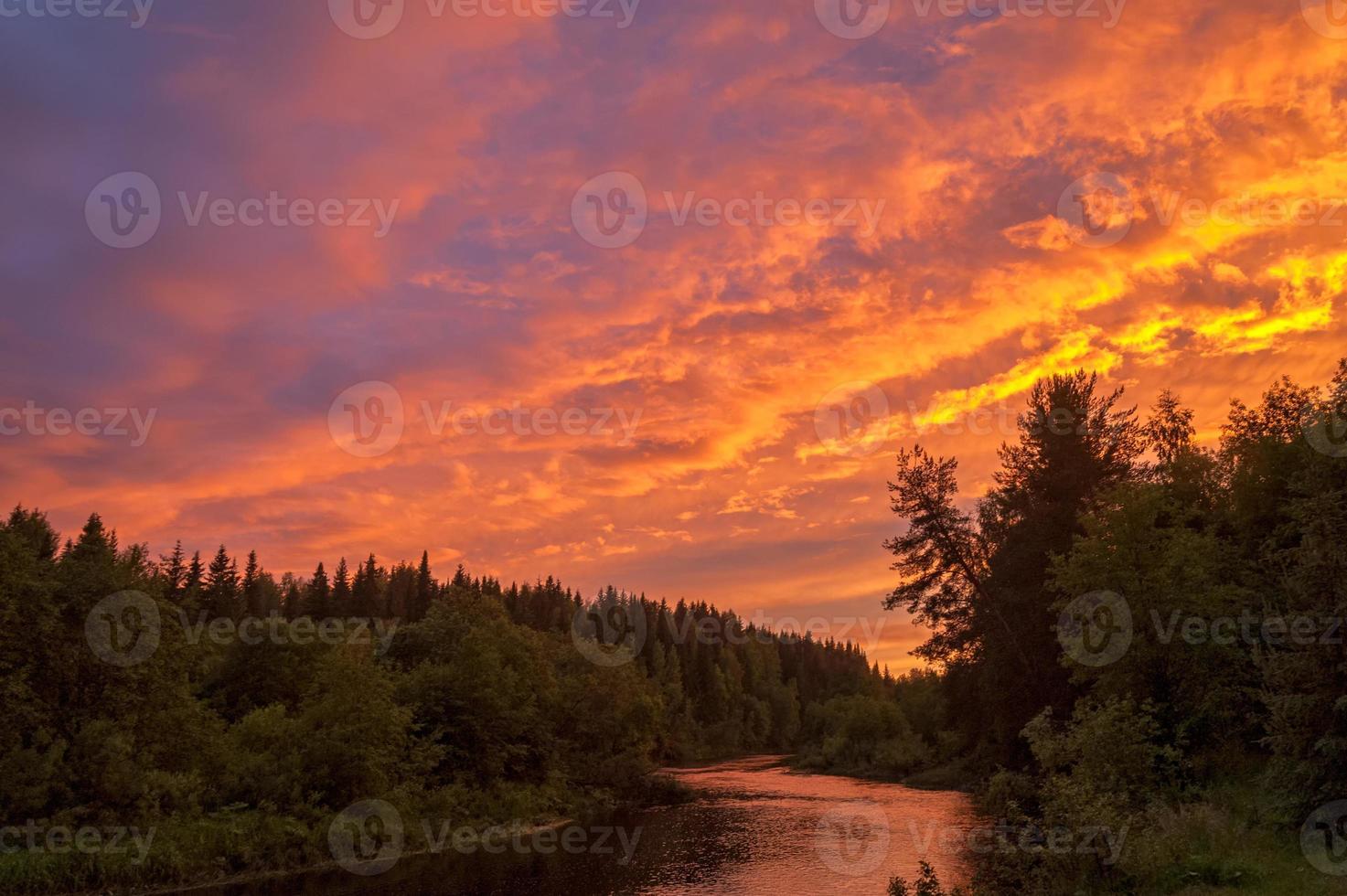brillante espectacular puesta de sol sobre el río con bosque a lo largo de la orilla del río foto