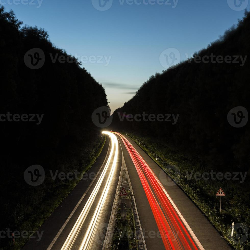 senderos de luz de coche en carretera al atardecer foto