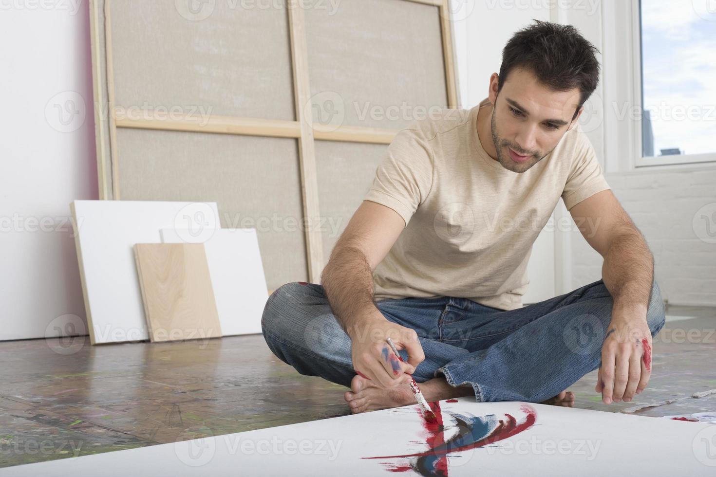 hombre pintando sobre lienzo en estudio foto