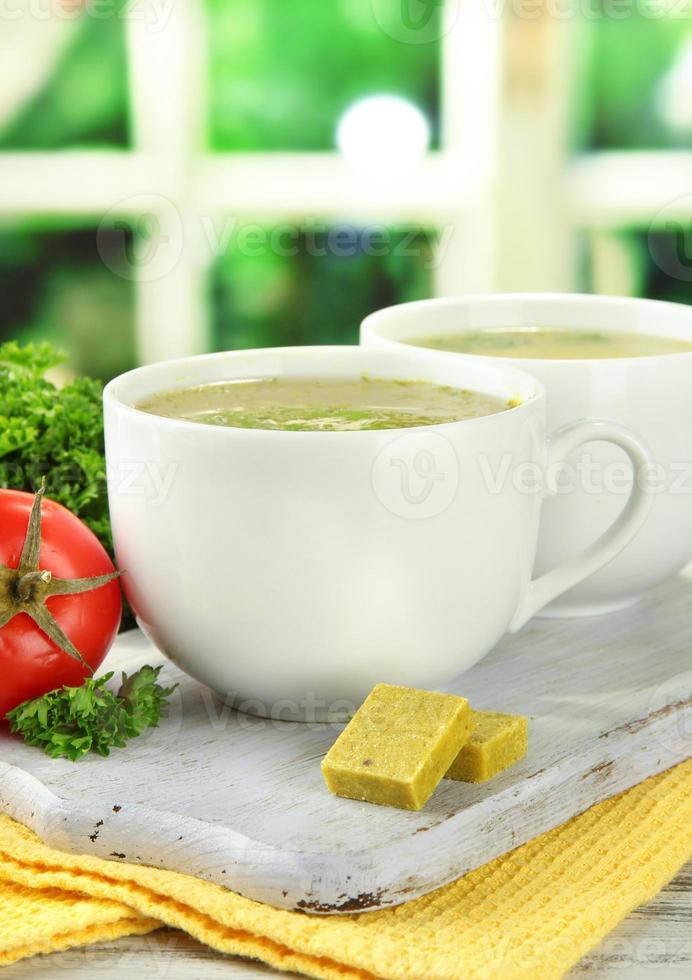 tazas de sopa con cubitos de caldo en la mesa de madera foto