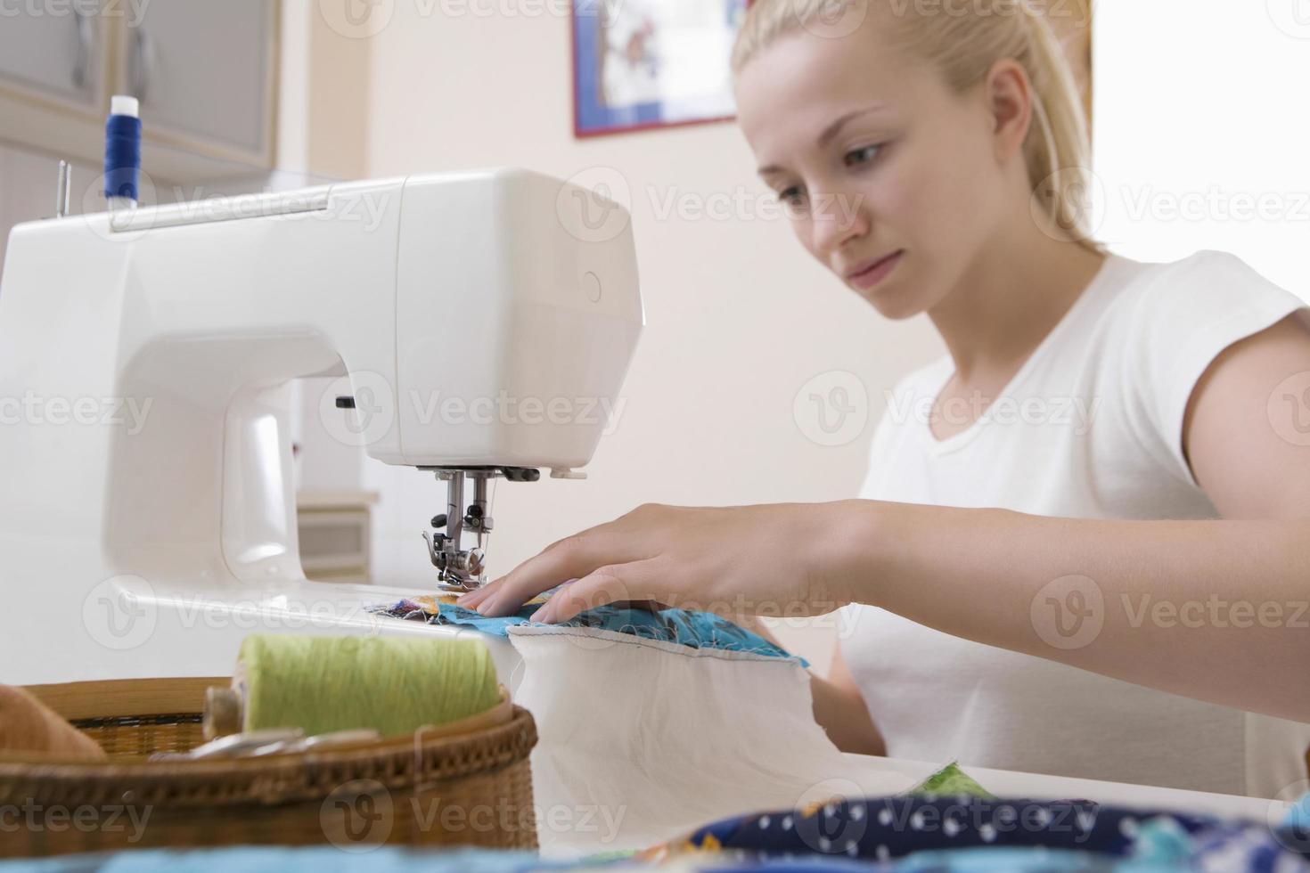 Mujer que trabaja con la máquina de coser en casa foto