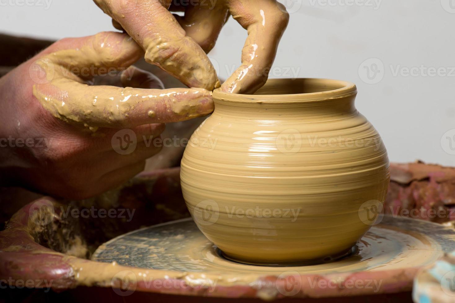 manos de un alfarero, creando una jarra de barro foto