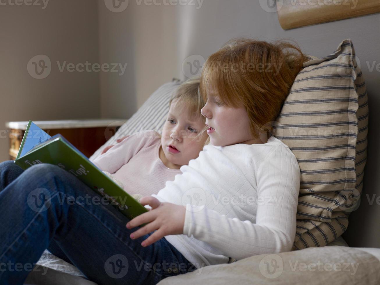 hermanas leyendo el libro en la cama foto