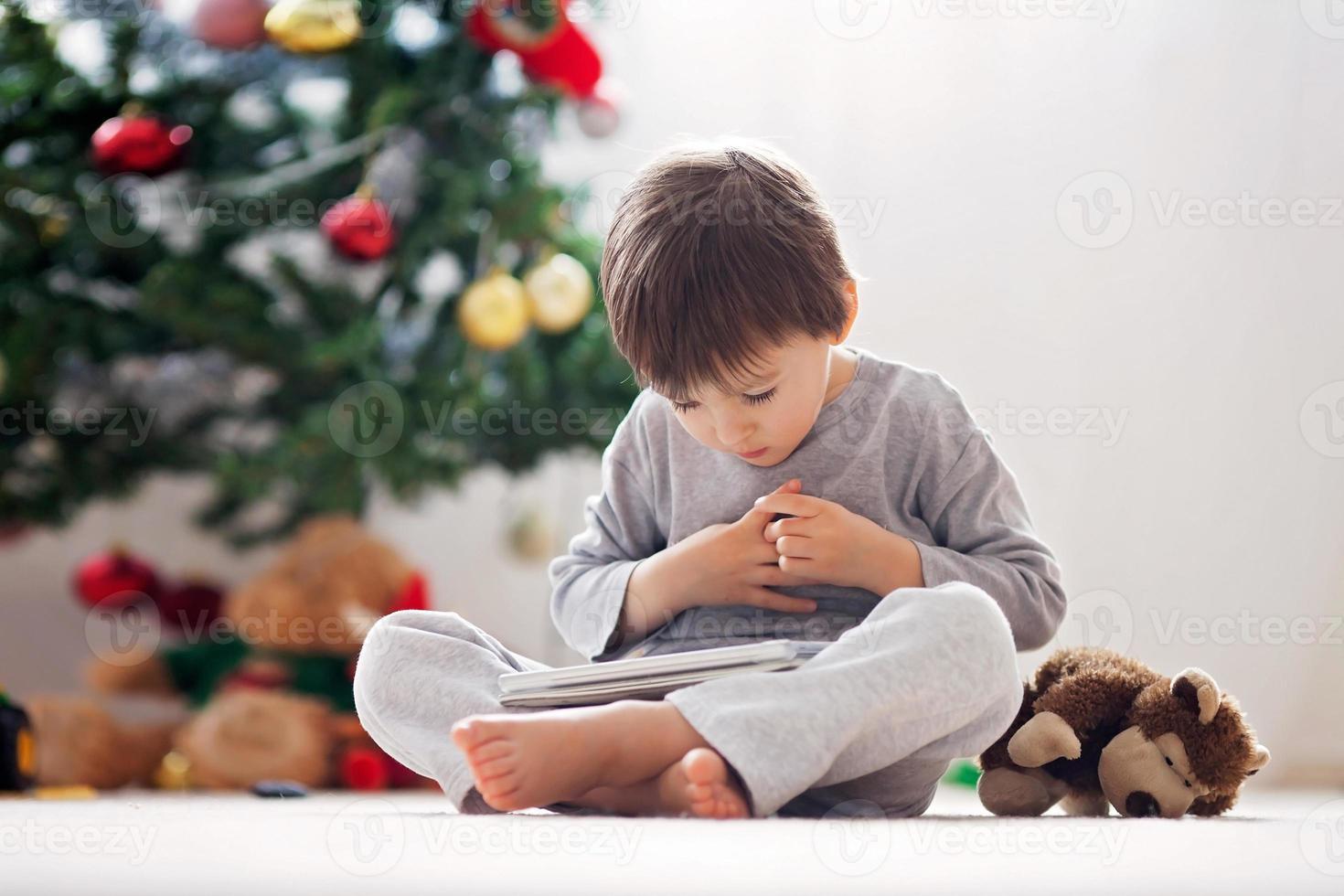 lindo niño y su mono juguete, jugando en tableta foto