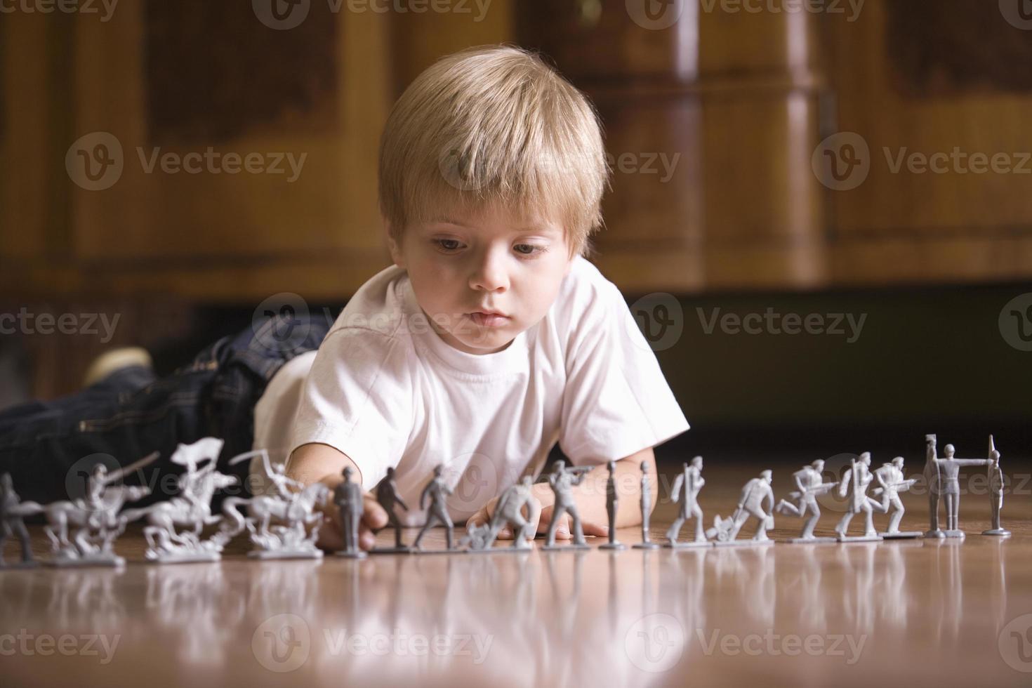 Niño jugando con soldados de juguete en el piso foto