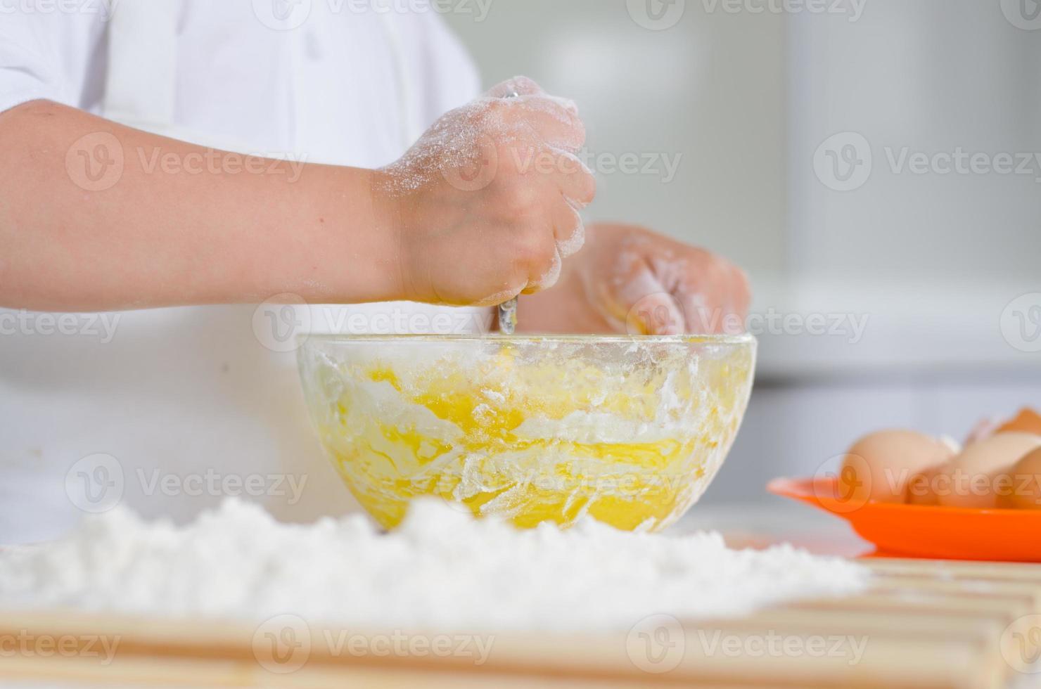 niño pequeño mezclando ingredientes de la torta foto