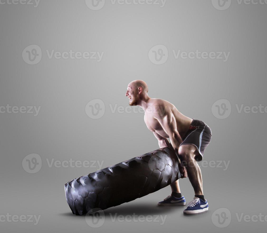 Joven atlético levantando un neumático sobre fondo gris studio foto