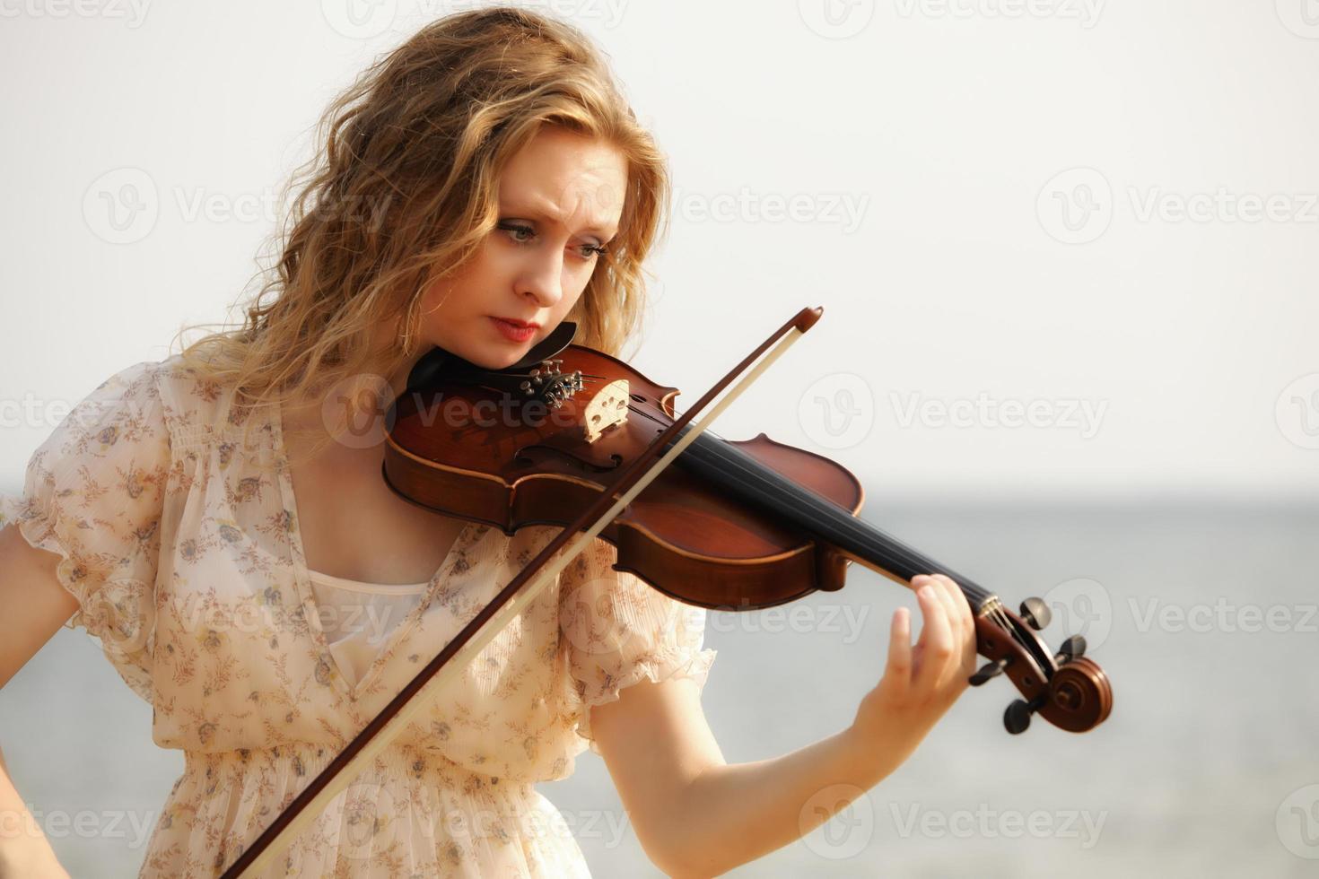 Retrato chica rubia con un violín al aire libre foto