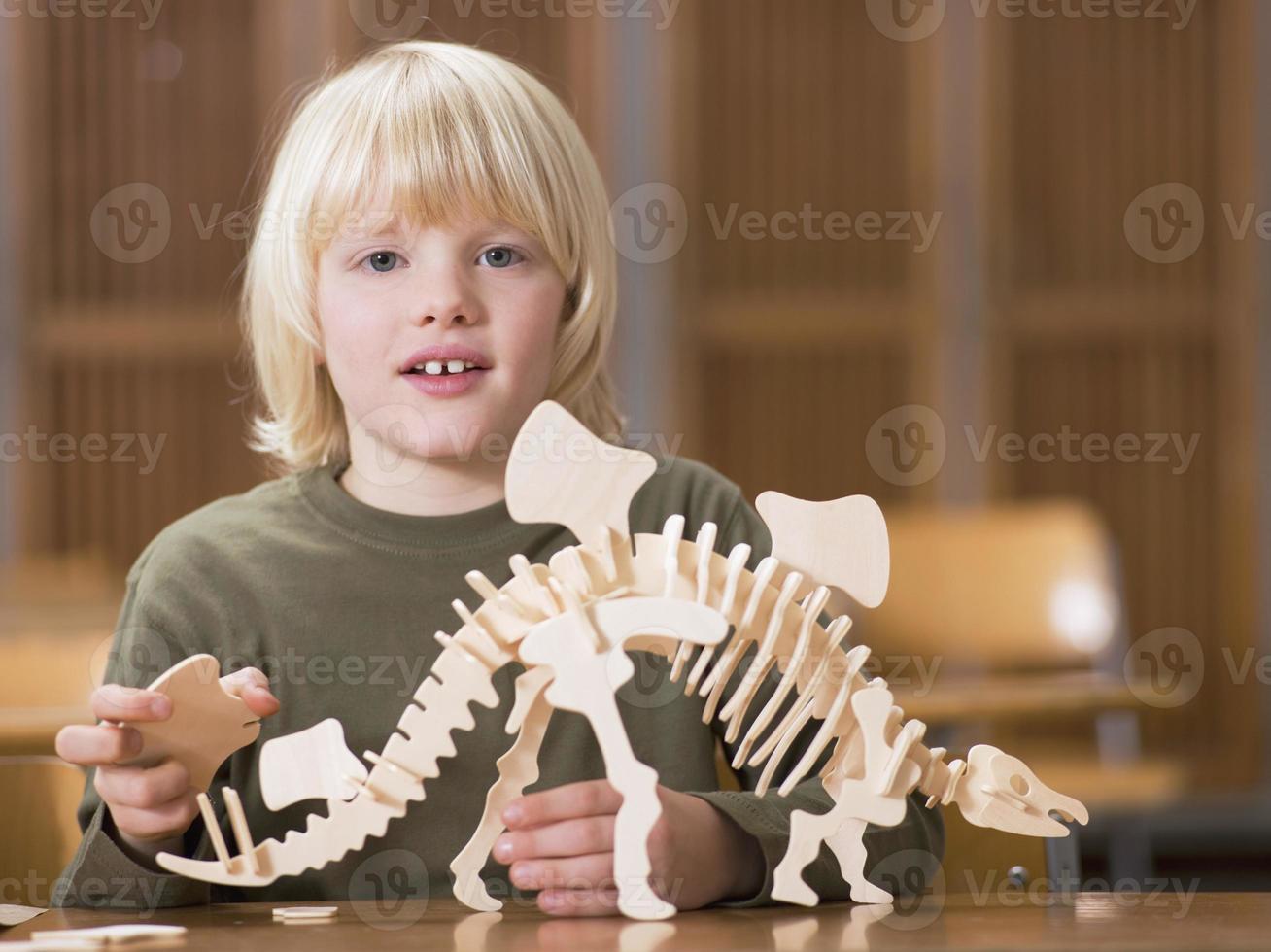 niño sentado con esqueleto de dinosaurio foto