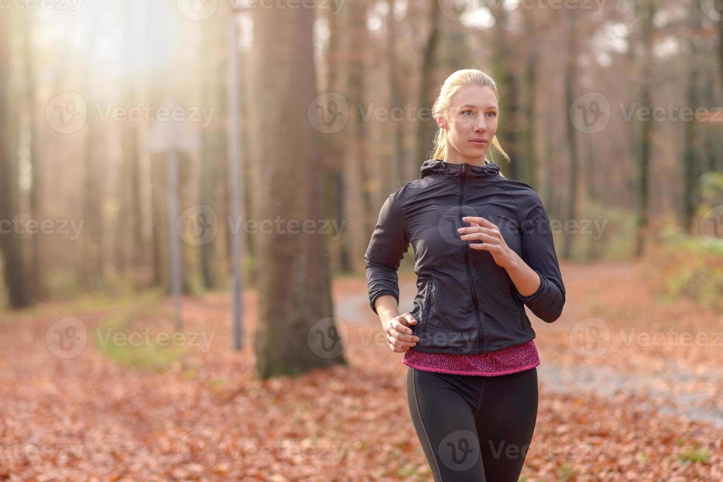 mujer joven bastante en forma para correr en el bosque foto