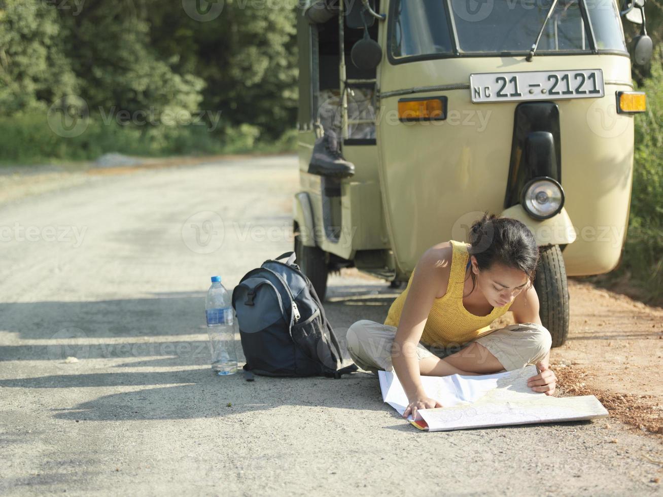 mujer leyendo mapa en carretera por autorickshaw foto